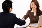 A smiling businesswoman shakes hands with a young businessman